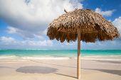 picture of atlantic ocean  - Wooden umbrella on empty sandy beach - JPG