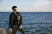 stock photo of jacket  - Handsome fashionable young man at the seaside along the shore overlooking the ocean or sea with his black leather jacket looking far away - JPG