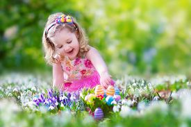 stock photo of bunny costume  - Adorable curly toddler girl in a pink summer dress playing with Easter eggs during egg hunt in a sunny garden with first white spring flowers - JPG