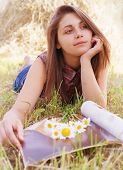 image of haystack  - portrait of a pretty girl with a magazine and a bouquet of daisies on a background of haystacks - JPG