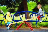 foto of seesaw  - cute kids having fun on seesaw at playground - JPG