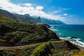 stock photo of atlantic ocean  - Road near coast or shore of Atlantic ocean with mountains and blue sky with clouds and skyline or horizon in Tenerife Canary island Spain at spring or summer - JPG