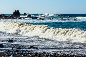 pic of atlantic ocean  - Waves and foam on wild stone beach on coast or shore of the Atlantic ocean with sky and rock on skyline or horizon in Tenerife Canary island Spain at spring or summer - JPG