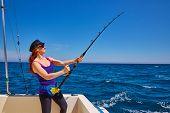 stock photo of fishing rod  - Beautiful woman girl fishing rod trolling in saltwater in a boat trolling - JPG