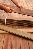 foto of carpenter  - Ipe decking installation with carpenter hands holding tropical wood slats - JPG