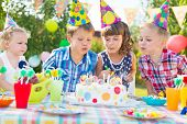 stock photo of blowing  - Kids celebrating birthday party and blowing candles on cake - JPG