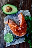 stock photo of over counter  - Fresh salmon steak avocado lime and parsley over old wooden texture  - JPG