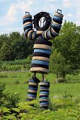 foto of grass area  - Large human looking sculpture made of tires and located in grass area - JPG