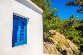 picture of greek-island  - Iconic blue wooden window against clear white wall - JPG