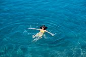 foto of top-hat  - Young woman in yellow swimsuit and big hat swimming and relaxing in the blue water sea - JPG