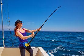 picture of rod  - Beautiful woman girl fishing rod trolling in saltwater in a boat trolling - JPG