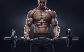 foto of shoulder muscle  - Closeup portrait of a muscular man workout with barbell at gym - JPG
