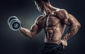 picture of shoulder muscle  - Handsome power athletic man in training pumping up muscles with dumbbell - JPG
