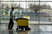 stock photo of hall  - A worker is cleaning the floor with machine - JPG