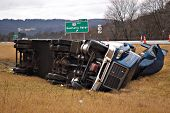 stock photo of tractor-trailer  - A tractor trailer rolls over and lands in the median in this big rig accident - JPG