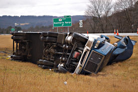 foto of tractor-trailer  - A tractor trailer rolls over and lands in the median in this big rig accident - JPG