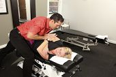 image of chiropractor  - Chiropractor adjusting a female patients neck on a chiropractic bench - JPG