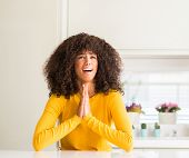 African american woman wearing yellow sweater at kitchen begging and praying with hands together wit poster