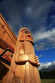 stock photo of indian totem pole  - Native American totem pole and wooden building - JPG