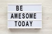 be Awesome Today Word On Lightbox Over White Wooden Background, From Above. Closeup. poster