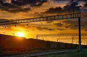 railroad infrastructure during beautiful sunset and colorful sky, railcar for dry cargo, transportat poster