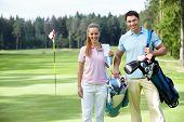 stock photo of golf bag  - Young couple on the golf course - JPG