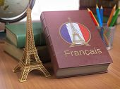 Learn and studiyng French concept. Book with  French flag and Eiffel tower on the table. 3d Iluustra poster
