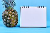 Ripe Pineapple And Blank Paper Notepad. Healthy Green Ananas And Empty Paper Notebook On Blue Backgr poster
