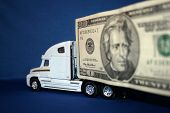 stock photo of semi-truck  - A semi truck with twenty dollar bill attatched to the side of the trailer.