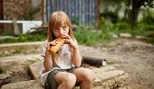 Poor Hungry Homeless Girl Eating A Piece Of Bread In The Dirty Alley, Selective Focus. Poverty And P poster