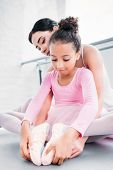 Cute African American Child In Pink Tutu Stretching While Training With Teacher In Ballet School poster