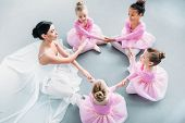 High Angle View Of Little Ballerinas And Ballet Teacher Exercising Together In Ballet School poster
