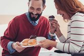 Tasty Lunch. Emotional Young Cheerful Couple Laughing While Looking At The Tasty Cakes On Their Plat poster