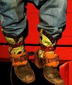 stock photo of buckaroo  - Well worn boots adorn the wranglers at rodeo in small county fair Idaho - JPG