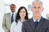 picture of follow-up  - Mature manager standing upright and followed by two serious employees - JPG