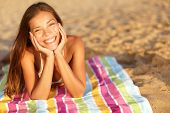 pic of vivacious  - Beautiful woman sunbathing on the beach lying on a towel facing the camera with her chin cupped in her hands and a lovely vivacious smile on her face - JPG