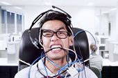 stock photo of crazy face  - Stress businessman biting cables at office due to busy schedule and deadlines - JPG