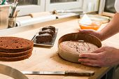 foto of torte  - Cook taking out layer cake from cake form - JPG