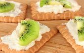 Crispbread with cheese and kiwi, on wooden background