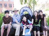 stock photo of biracial  - Father sitting with his biracial children and disabled son in wheelchair - JPG