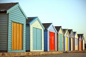 stock photo of row houses  - Brightly painted beach huts of houses in a row - JPG