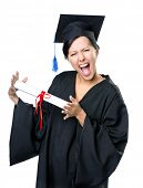 stock photo of school-leaver  - Graduating student in academic black gown and square cap with the diploma - JPG