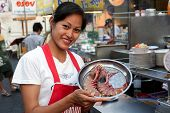 Thai waitress displaying tiger prawns