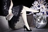 stock photo of nea  - woman in black dress and shoes is nea the christmas tree with splashes on the floor - JPG