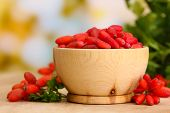 stock photo of barberry  - ripe barberries in wooden bowl with green leaves - JPG