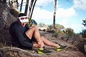 image of muscle strain  - running injury for trail runner on mountain twisted ankle - JPG