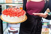 pic of confectioners  - Female confectioner presenting tray of cake in bakery or pastry shop - JPG
