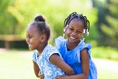 picture of sisters  - Outdoor portrait of a cute young black sisters laughing - African people
