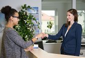 stock photo of over counter  - Two smiling women greet each other with handshake over a counter in the office - JPG