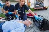 stock photo of paramedic  - Paramedics checking pulse of unconscious senior man lying on street - JPG